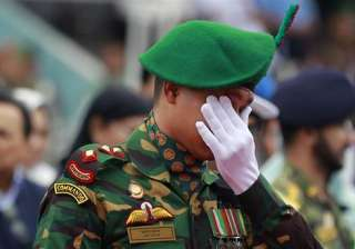 A Bangladeshi soldier reacts as people pay their respects to the Bangladeshi victims of the attack on Holey Artisan Bakery, at a stadium in Dhaka, Bangladesh.