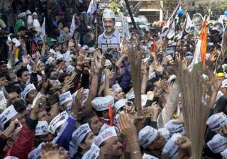 Supporters of the Aam Aadmi Party, holds cut outs of their leader Arvind Kejriwal and their party symbol, the broom, as they celebrate the party's victory in New Delhi.