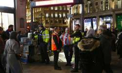 Police officers and Transport for London workers stand at