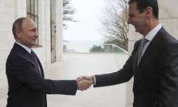 Vladimir Putin shakes hand with Bashar Assad in the