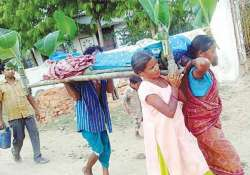 Two sisters carry the body of their mother in a village in