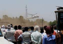 A crowd looks on as the helicopter with Mahrashtra CM on