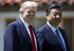 File pic - Trump and Jinping walk together after their