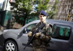 A French soldier stands guard near the site where a vehicle