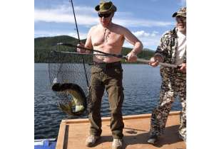 Putin holds his trophy catch while fishing during a mini-break in Siberian Tyva