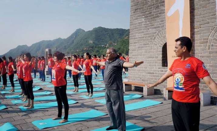 Indians and Chinese practice yoga at Great Wall