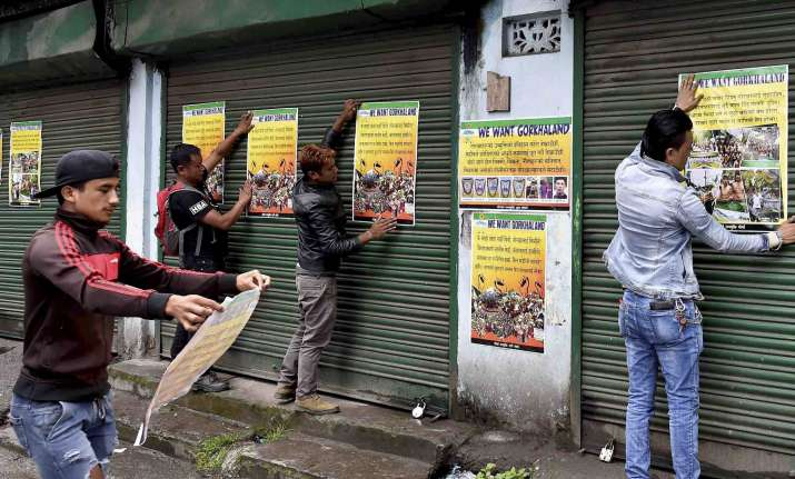 GJM activists paste party posters during indefinite strike