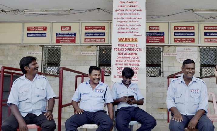 Guards sitting near the ticket counter of a closed cinema