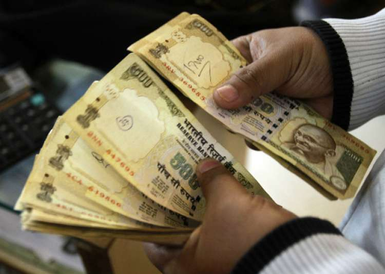 File pic - A man counts now scrapped Rs 500 notes - India Tv