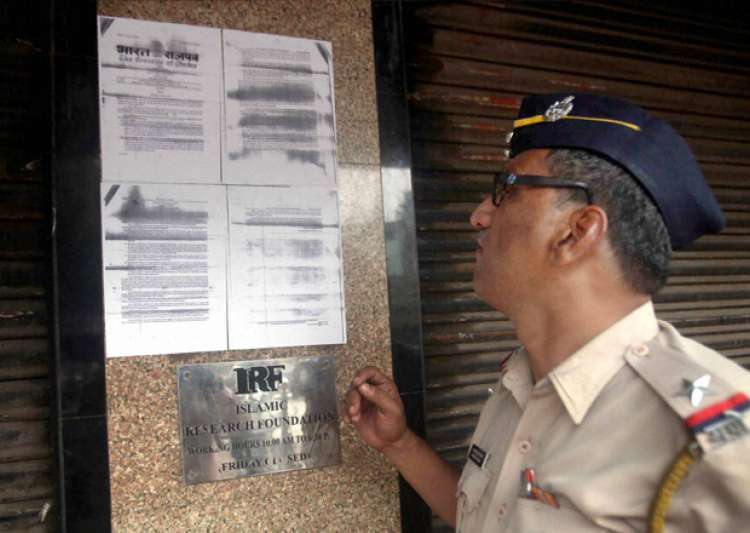 A police constable reads the ban order pasted outside IRF- India Tv