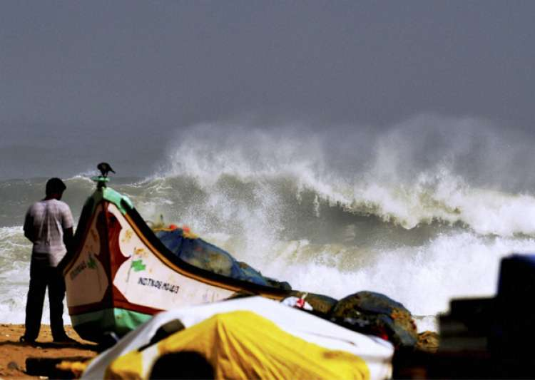 A man stands near boats as waves break on the cost of the