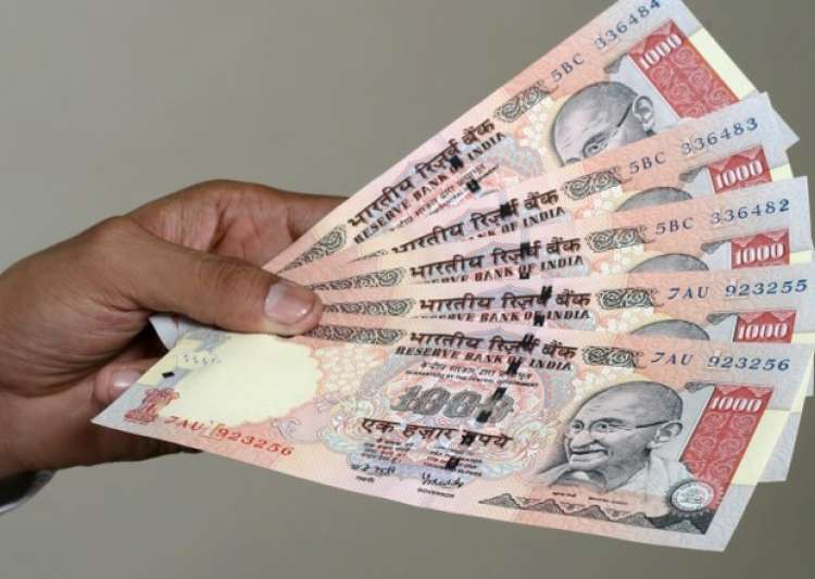 File pic - A man displays scrapped Rs 1,000 notes