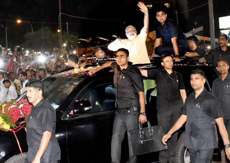 PM Modi waves at people during a road show in Surat on