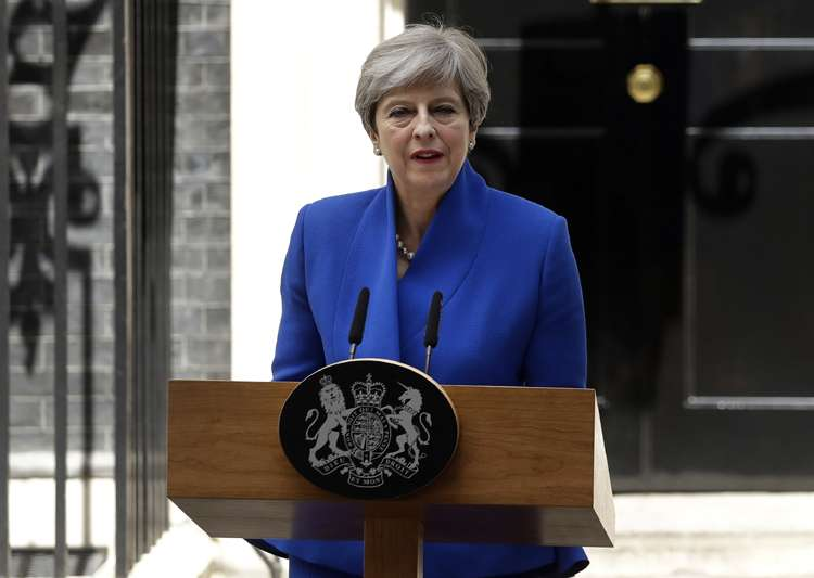 Theresa May, weakened after elections, remains as Britain's prime minister