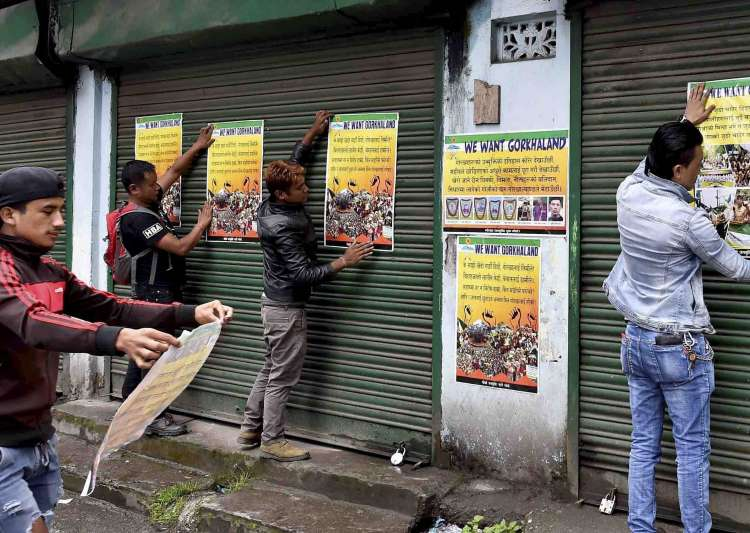 GJM activists paste party posters during indefinite strike- India Tv