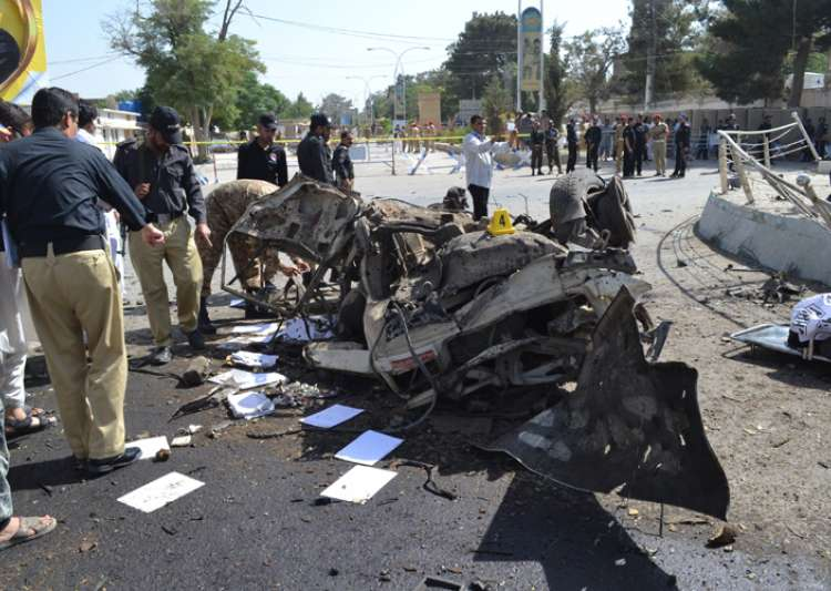 Pakistani police officers examine the site of an explosion