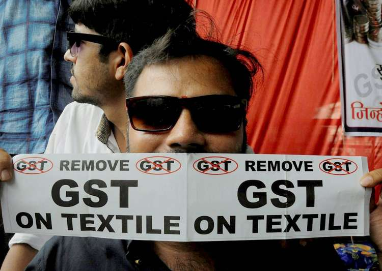 A textile trader with anti-GST poster during a protest in- India Tv