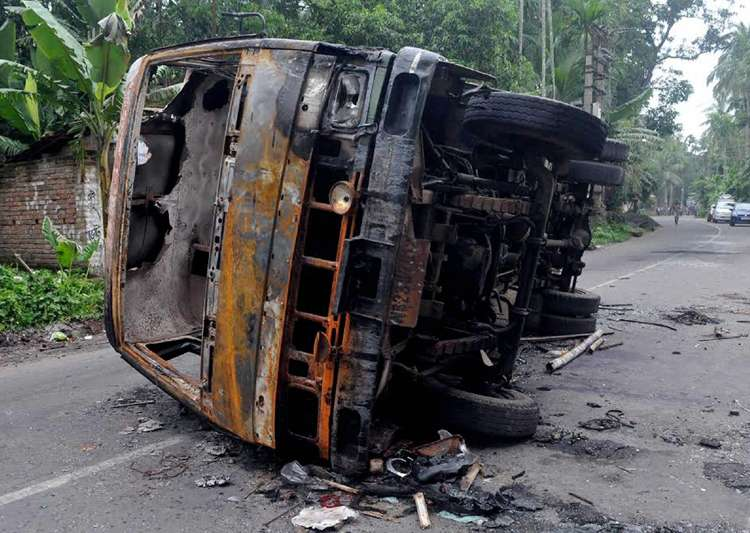 A burnt vehicle seen at a road after a communal riot at