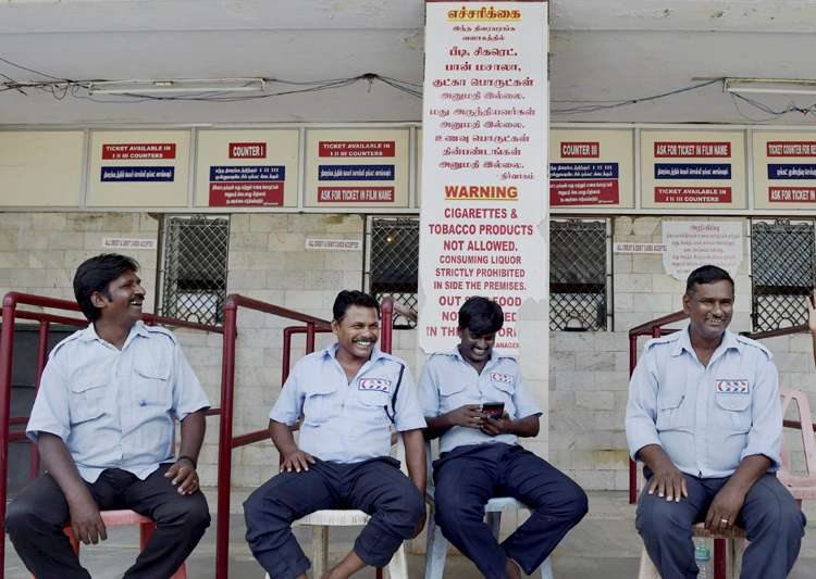 Guards sitting near the ticket counter of a closed cinema- India Tv
