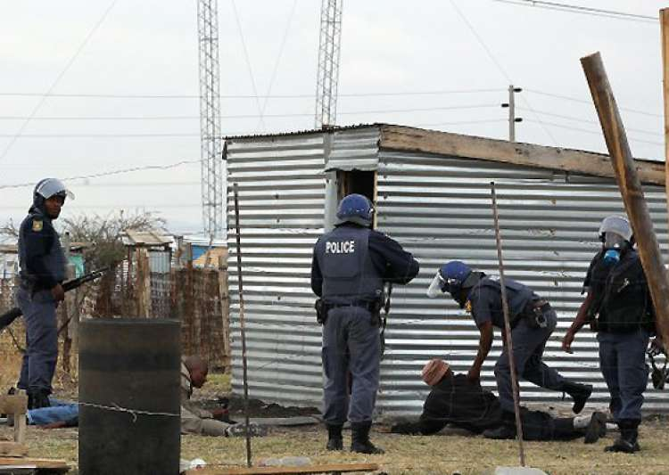 safrican police fire gas force people into shacks- India Tv