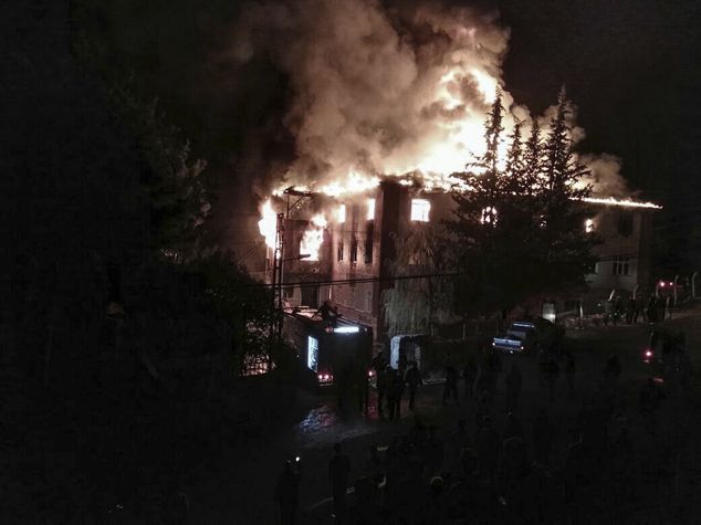 Flames rise from a fire in a school dormitory, in Aladag,