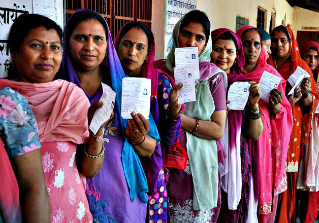 File pic - Women show their voting slips as they wait to