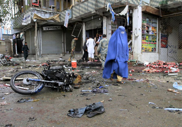 File - Afghan woman walks past site of suicide attack in