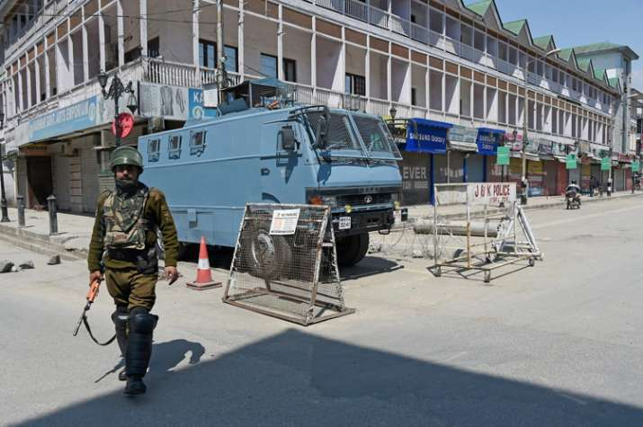 Security jawan stands guards in a deserted street in