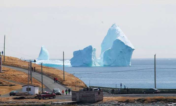 India Tv - A 150-feet iceberg floats past Canadian village