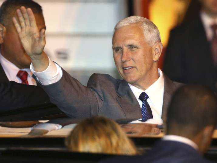 Mike Pence waves as he gets into his car after arriving in