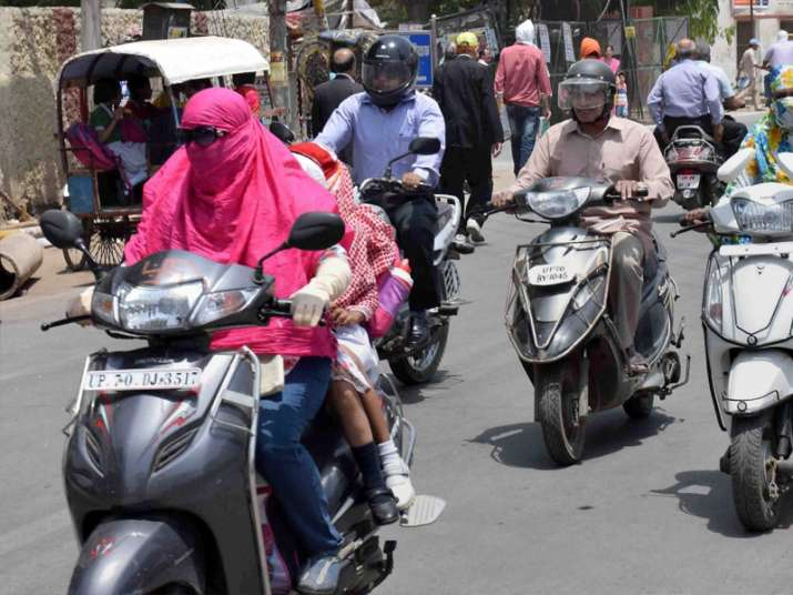 People cover their faces to protect themselves from heat in