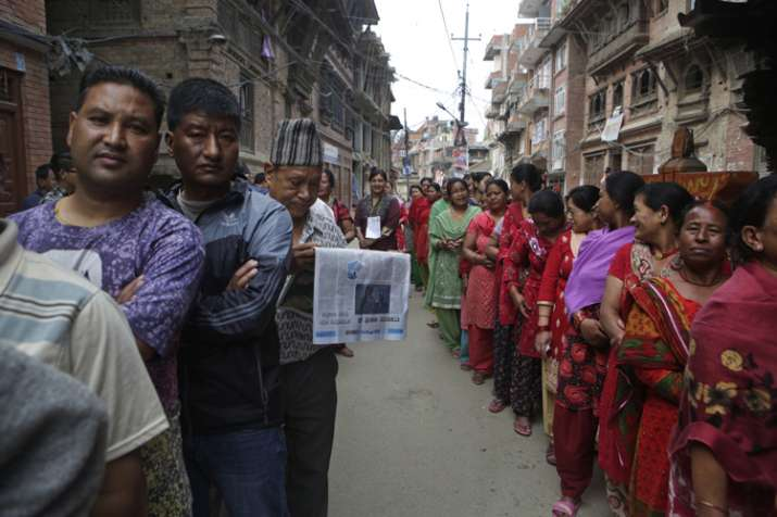 Nepalese stand in a queue to cast their votes during the