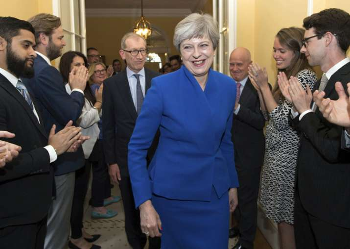 Britain's PM Theresa May applauded by staff as she returns