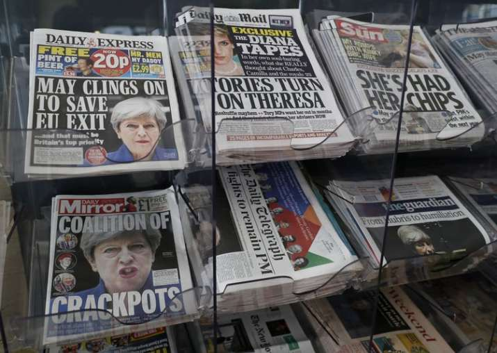 Newspapers fronted with photos of May are displayed at a