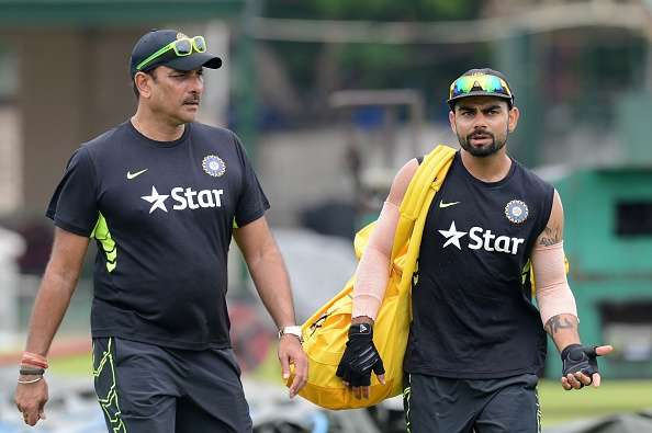 Ravi Shastri (L) and captain Virat Kohli talk during a