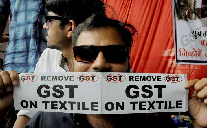 A textile trader with anti-GST poster during a protest in