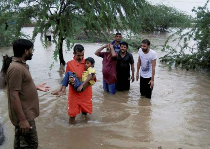 People wade through floodwaters after heavy rainfall in
