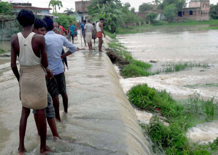 India Tv - Motihari: People at a flooded village in East Champaran district