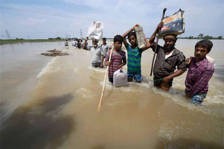 Flood-affected villagers shift with their belongings in