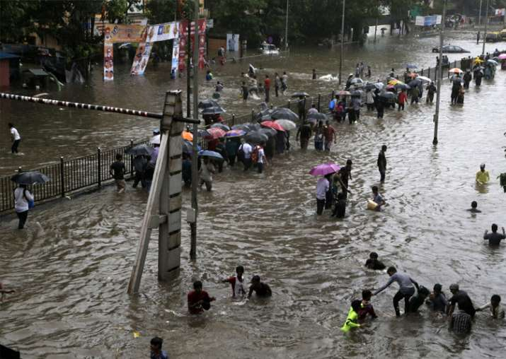 India Tv - People walk through a waterlogged street following heavy rains in Mumbai
