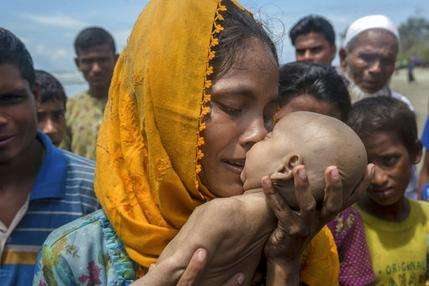 A Rohingya Muslim woman kisses her infant son. Ph