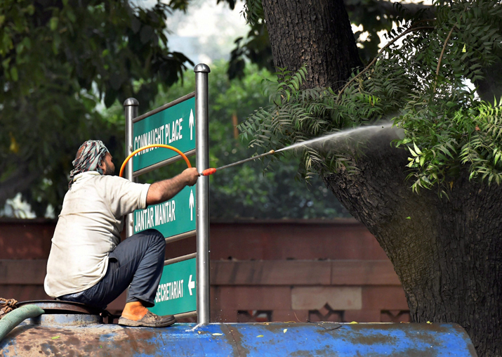 India Tv - A NDMC worker sprays water on a tree to combat toxic smog and dust, and improve the air quality of the capital, at Parliment Street in New Delhi