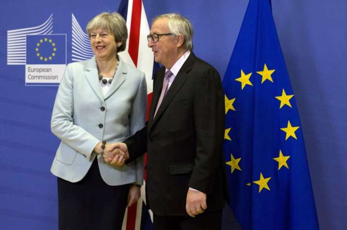 British PM Theresa May, left, is greeted by European