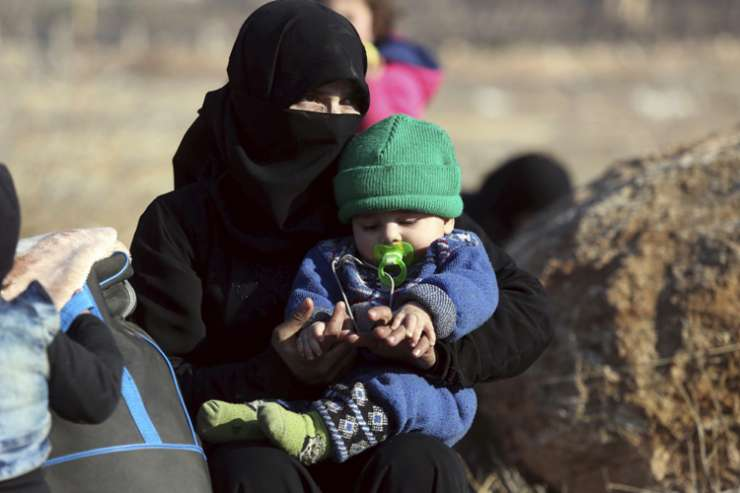 A Syrian woman with child evacuated from Aleppo arrive at a refugee camp
