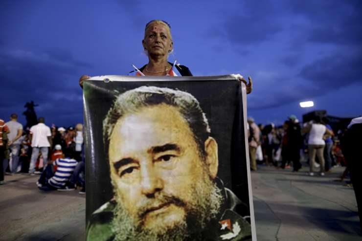 A woman holds a picture of Fidel Castro before a rally honoring Cuba's leader