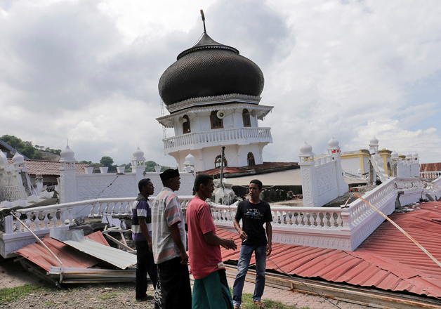Men inspect a collapsed mosque after an earthquake in Aceh province
