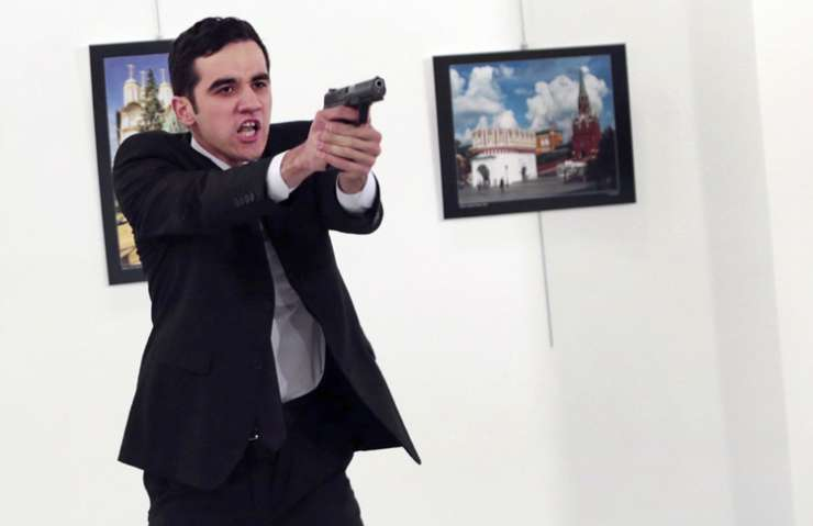 Gunman points his gun, after shooting the Russian envoy to Turkey