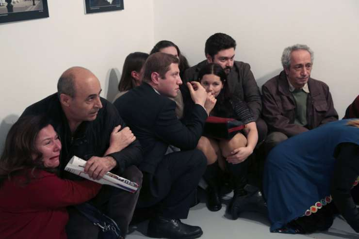 People crouch in a corner after Karlov was shot at a photo gallery in Ankara