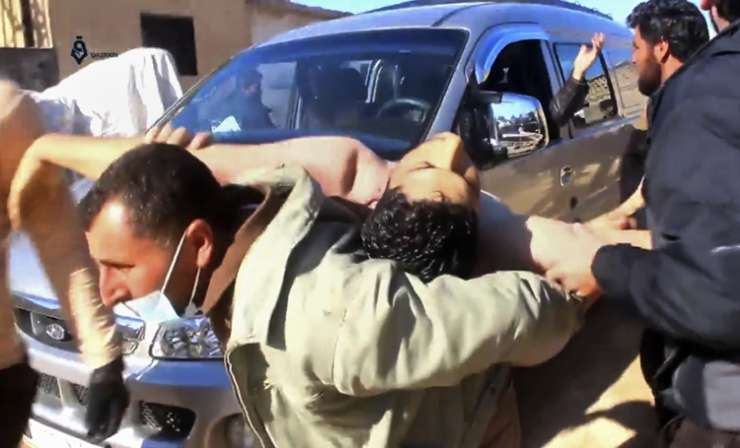 India Tv - Syrian man carrying a man after a suspected chemical attack in Idlib