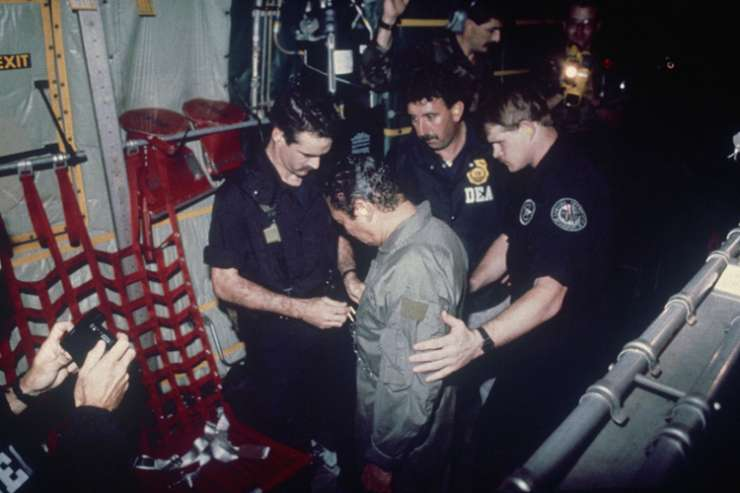 In this Jan 4, 1990 photo, US DEA agents place chains around Noriega's waist